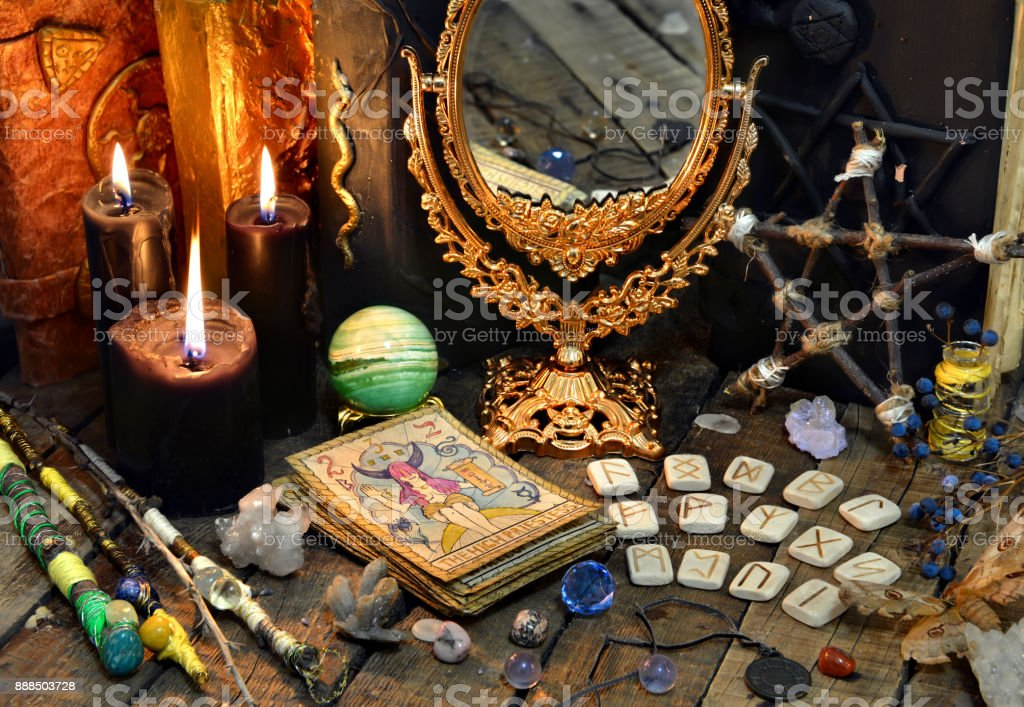 Tarot cards, magic wands, runes, black candles with mirror and old book stock photo