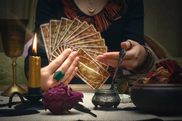 Tarot cards on fortune teller desk table. Future reading concept. Tarot cards. Future reading. Woman fortune teller holding in hands a deck of tarot cards and shows on it. arcane stock pictures, royalty-free photos & images