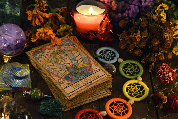 Tarot cards with chakra decorations, herbs and burning candle. stock photo
