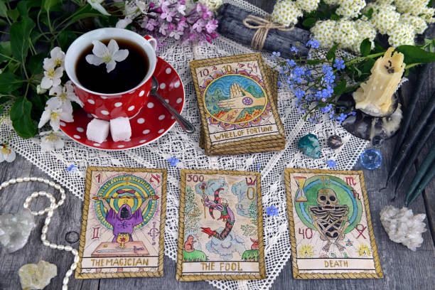Tarot cards with cup of tea, flowers and black candles on planks stock photo