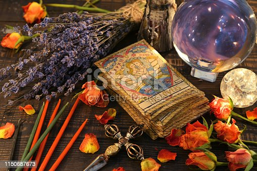 Tarot cards with magic crystal ball, candles and lavender flowers. Wicca, esoteric, divination and occult background with vintage magic objects for mystic rituals
