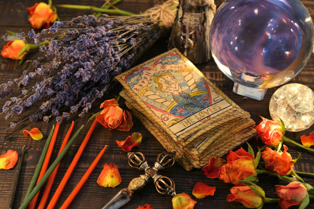 Tarot cards with magic crystal ball, candles and lavender flowers. stock photo