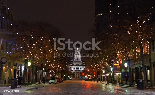 A nighttime view of the Tarrant County Courthouse in Fort Worth, Texas, from the middle of Main Street. The ground is coated in ice due to a rare storm that had previously passed through.