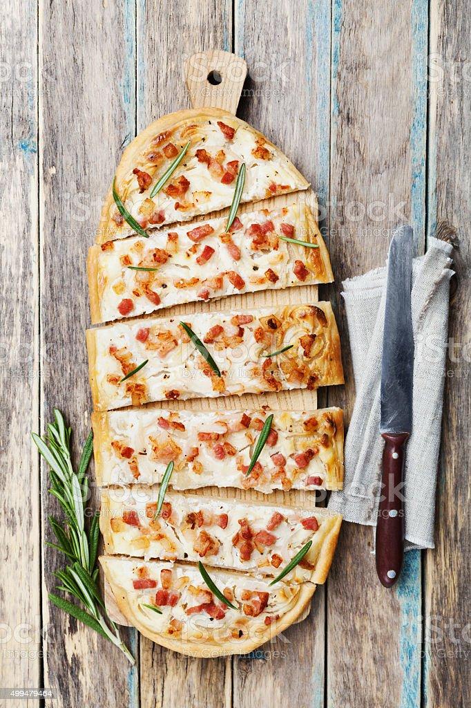 Tart Flambe or Flammkuchen on wooden cutting board stock photo