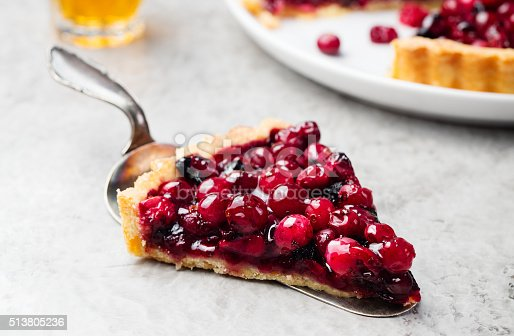 Tart, pie, cake with jellied fresh cranberries, bilberries and winter spices on a grey stone background. Copy space