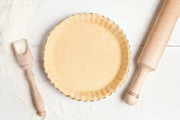 Tart pie preparation, dough with yeast and rolling pin on stock photo