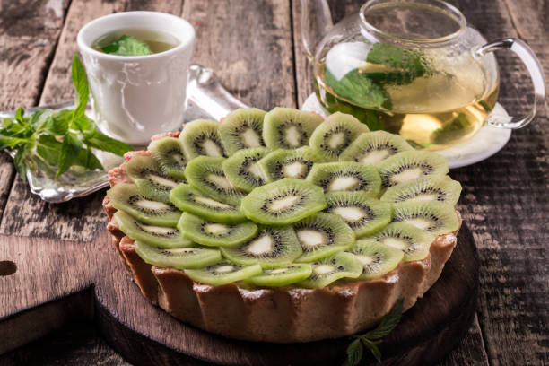 Tart with kiwi and whipped cream on wooden vintage table stock photo