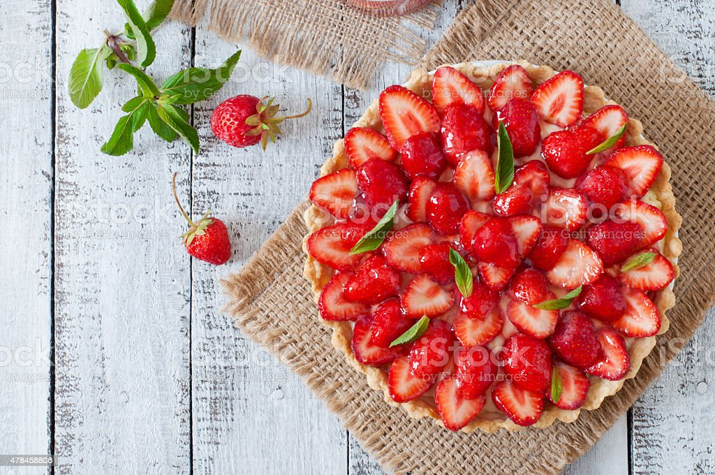 Tart with strawberries and whipped cream decorated with mint leaves stock photo
