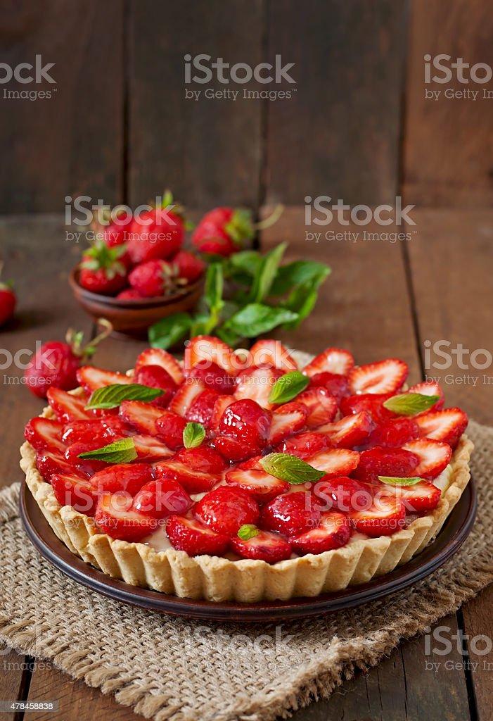 Tarte mit Erdbeeren und Sahne, dekoriert mit Minzblättern – Foto