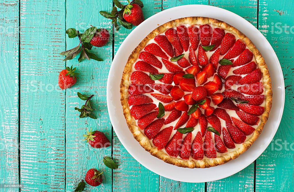 Tart with strawberries and whipped cream decorated with mint leaves.