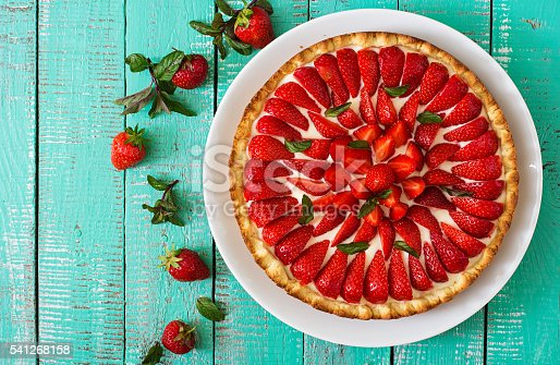 istock Tart with strawberries and whipped cream decorated with mint leaves. 541268158