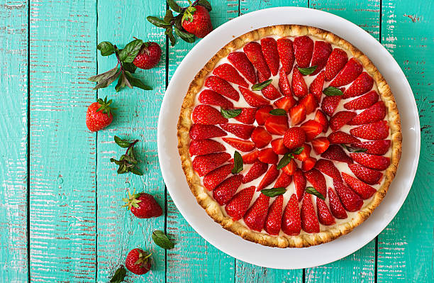 tart with strawberries and whipped cream decorated with mint leaves. - sommertorten stock-fotos und bilder