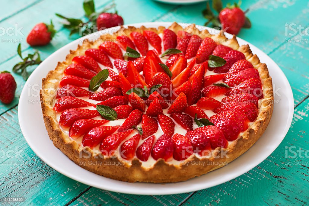 Tart with strawberries and whipped cream decorated with mint leaves. – Foto