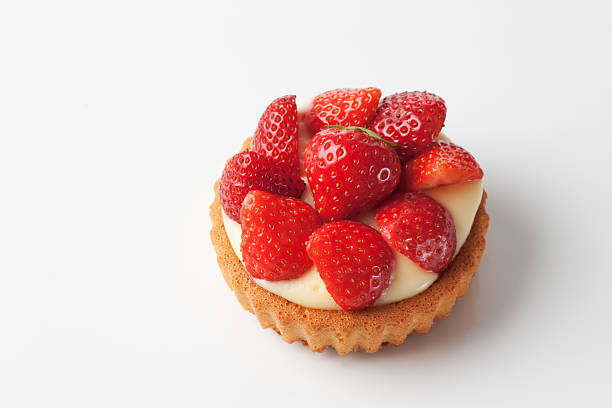 Tartlet filled with vanilla custard strawberries on top on white stock photo