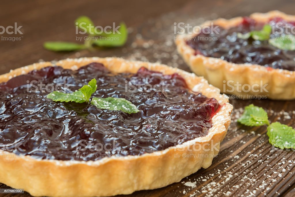 Tartlet with blackberry jam and mint stock photo
