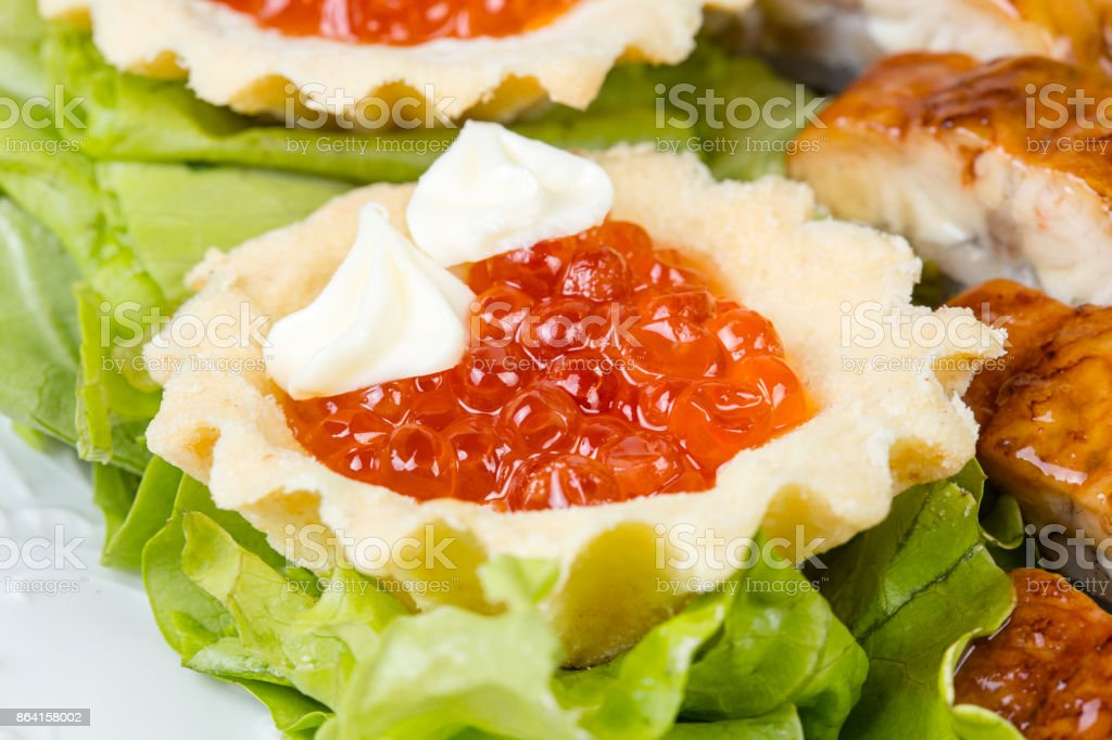 Tartlet with red caviar, salad and fish royalty-free stock photo