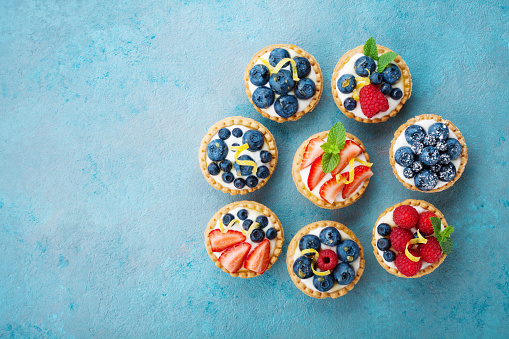 Tartlets or cake with cream cheese and berry on turquoise table from above. Сolorful pastry dessert.