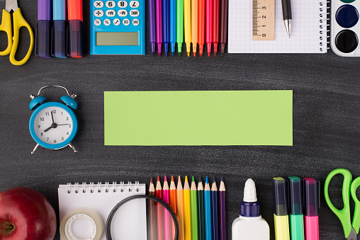istock Task deadline concept. School project concept. Top above overhead view photo of clock with green note beside and colorful stationery above and below it isolated on blackboard with copyspace 1255265161