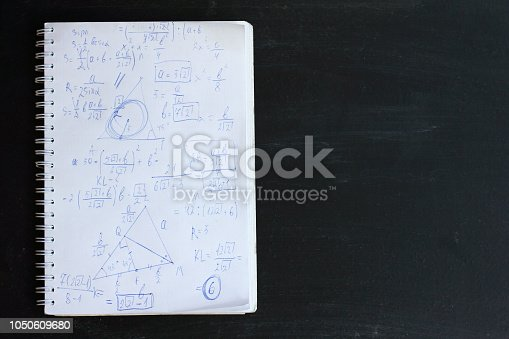 notebook with various mathematical and geometric formulas on the background of a school board
