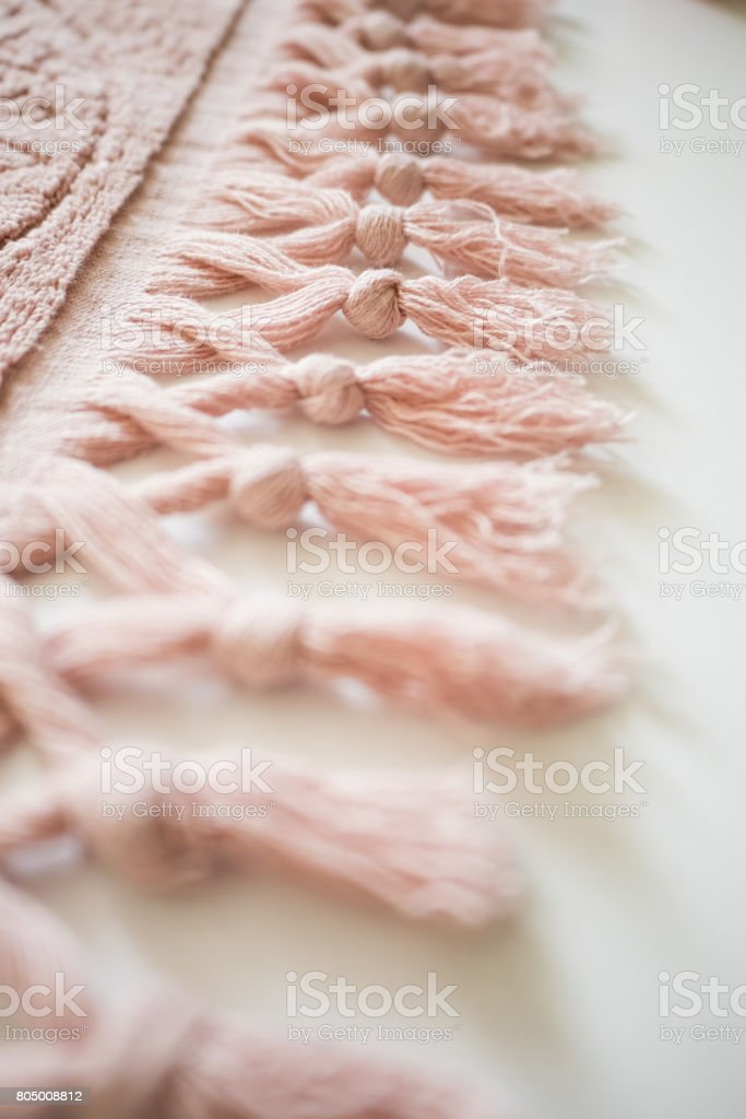 Tassels of a textile on a white background. Pink towel stock photo