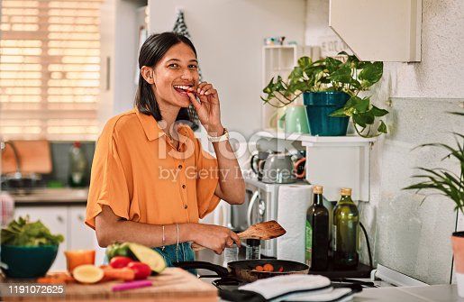 Shot of a happy young woman preparing a healthy meal at home