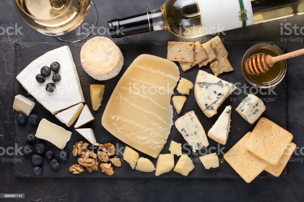 Tasting cheese dish on a dark stone plate. Food for wine and romantic date, cheese delicatessen on a black concrete background. Top view stock photo