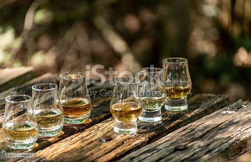 Tasting of different Scotch whiskies on outdoor terrace, dram of whiskey close up
