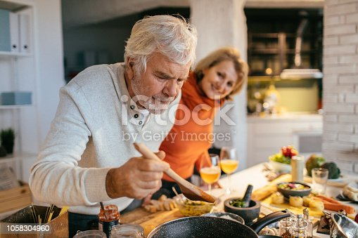 Photo of a senior couple tasting the food they have prepared together