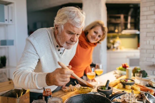 Tasting the food they've prepared Photo of a senior couple tasting the food they have prepared together hobbies stock pictures, royalty-free photos & images