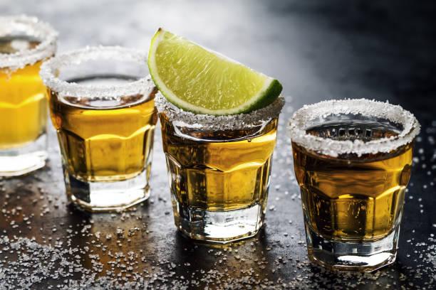 Savoureux alcool boisson cocktail tequila au citron vert et de sel sur fond sombre vibrante. Gros plan. Horizontal. - Photo