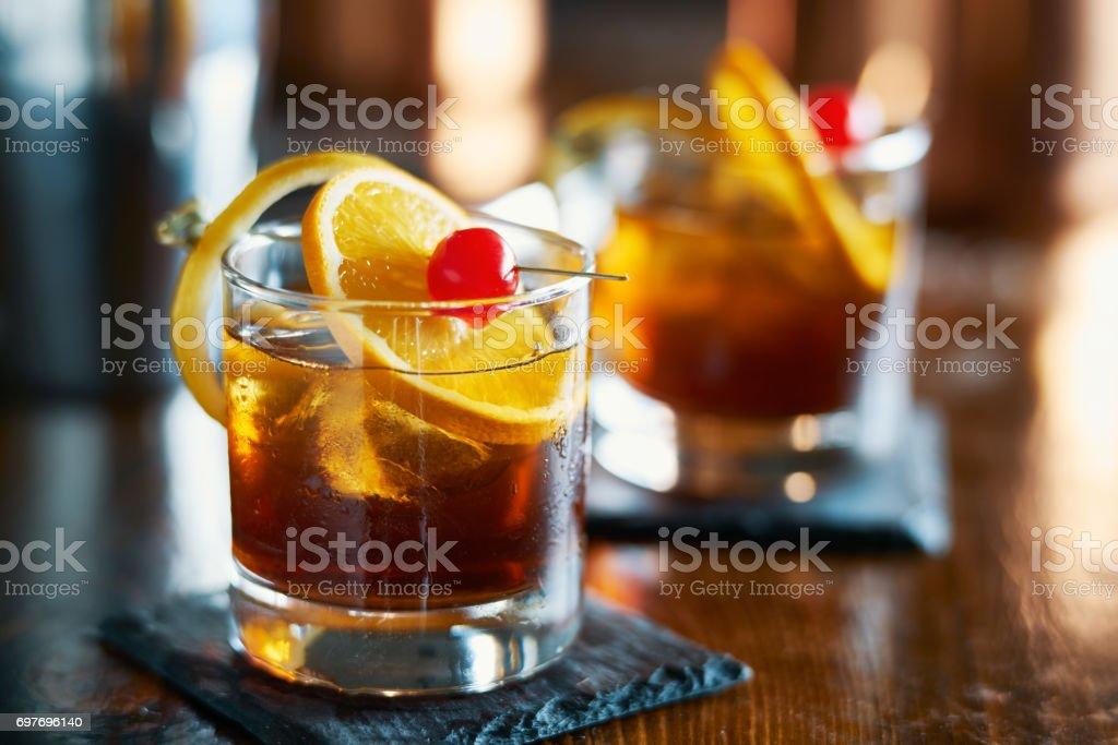 tasty alcoholic old fashioned cocktail with orange slice, cherry, and lemon peel garnish stock photo