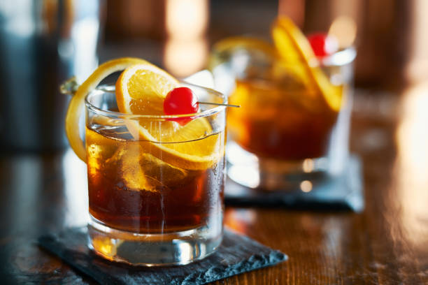 tasty alcoholic old fashioned cocktail with orange slice, cherry, and lemon peel garnish - foto stock
