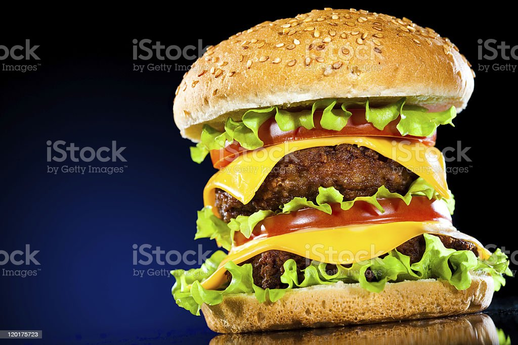 Tasty and appetizing hamburger on a darkly blue royalty-free stock photo