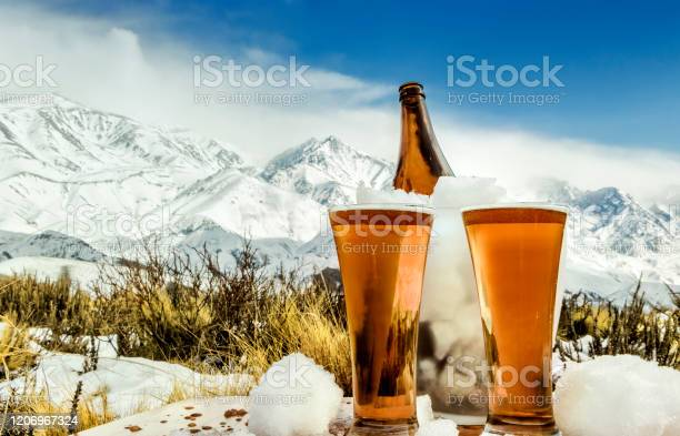 Photo of Tasty and fresh craft red beer at the foot of the snowy mountain.