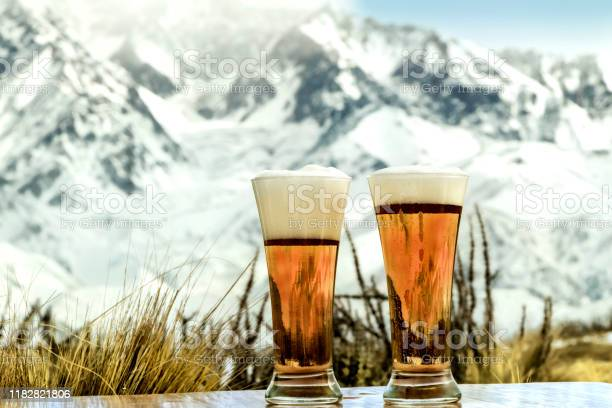 Photo of Tasty and fresh red beer at the foot of the snowy mountain.