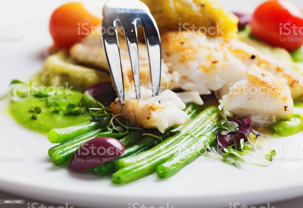Tasty and healthy restaurant dish of grilled fish with vegetables royalty-free stock photo