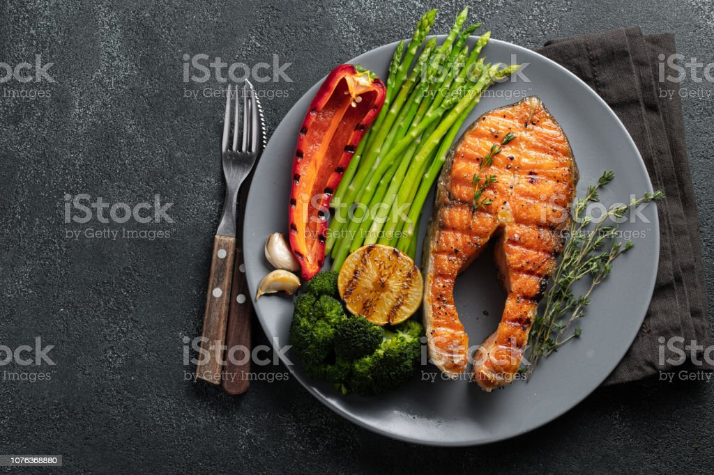 Tasty and healthy salmon steak with asparagus, broccoli and red pepper on a gray plate. Diet food on a dark background with copy space. Top view. Flat lay royalty-free stock photo