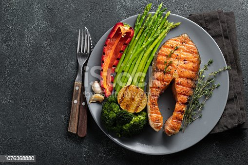 Tasty and healthy salmon steak with asparagus, broccoli and red pepper on a gray plate. Diet food on a dark background with copy space. Top view. Flat lay.
