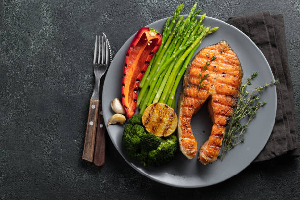 Tasty and healthy salmon steak with asparagus, broccoli and red pepper on a gray plate. Diet food on a dark background with copy space. Top view. Flat lay stock photo