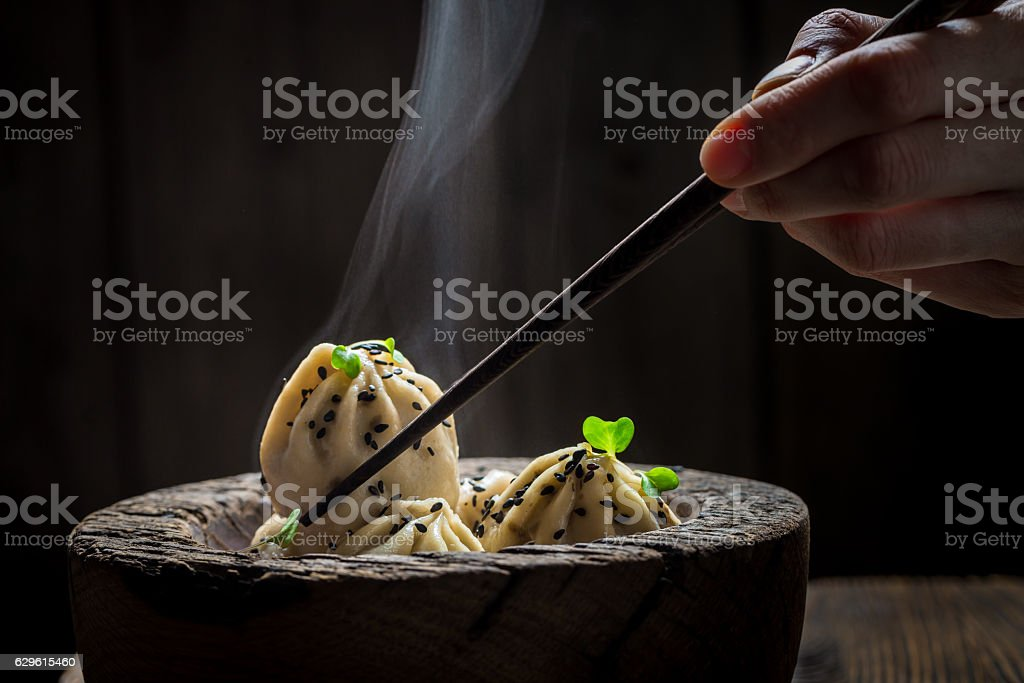 Tasty and hot chinese dumplings in wooden bowl stock photo