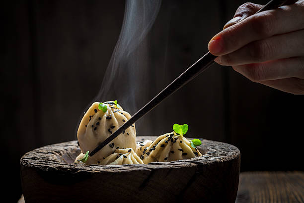 tasty and hot chinese dumplings in wooden bowl - chinese food stock photos and pictures