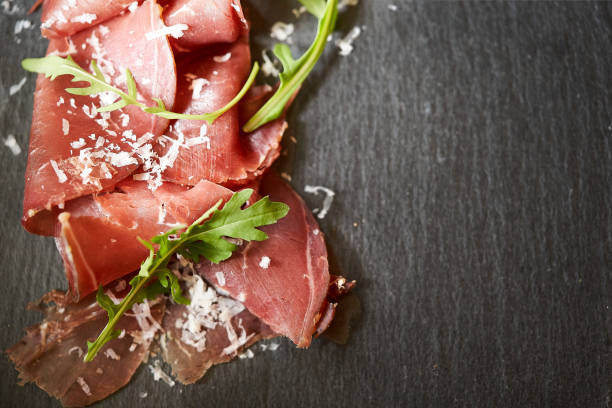 tasty appetizing classic italian bresaola with arugula and parmesan on black ardesia background. view form above. top view. horizontal. with copy space for text. - bresaola foto e immagini stock