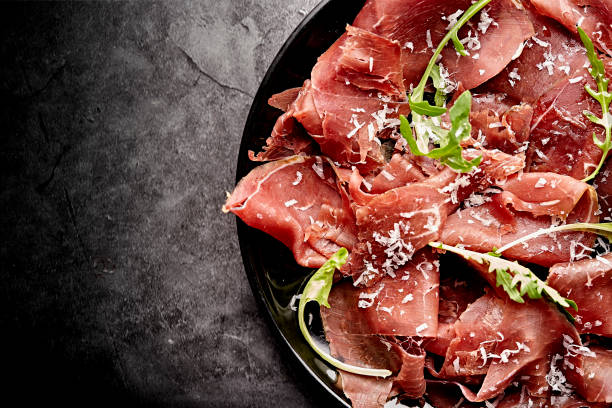 tasty appetizing classic italian bresaola with rocket salad and parmesan on black plate on black background. view form above - bresaola foto e immagini stock