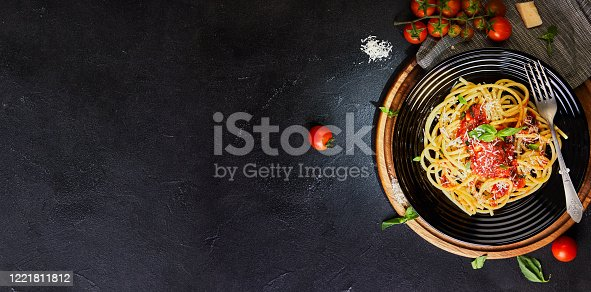 Tasty appetizing classic Italian pasta spaghetti with tomato sauce, parmesan and basil on a plate on a dark table. Top view, horizontal. Flat lay. Copy space. Banner