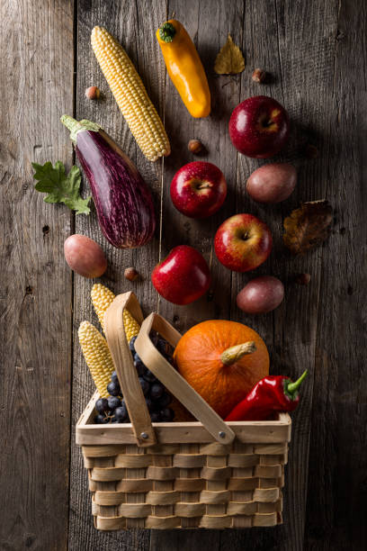 Tasty appetizing fresh autumn seasonal vegetables fruits in basket on wooden old background top view above copy space stock photo