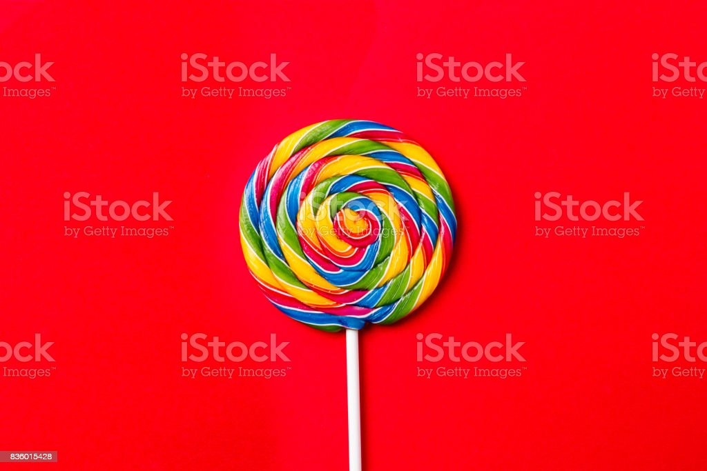 Tasty appetizing Party Accessory Sweet Treat Swirl Candy Lollypop on Bright Red Background Top View Minimalism Fashion Conceptual stock photo