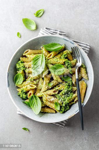 Tasty appetizing wholegrain pasta with pesto sauce, parmesan cheese and basil served on plate on grey background.