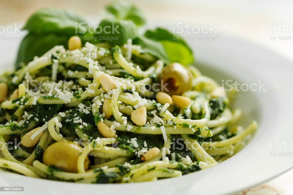 Tasty Beautiful Pasta Closeup with Spinach, Cheese, Olives, Basil and Nuts. stock photo