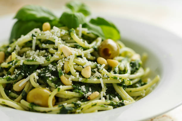 tasty beautiful pasta closeup with spinach, cheese, olives, basil and nuts. - italian food stock photos and pictures