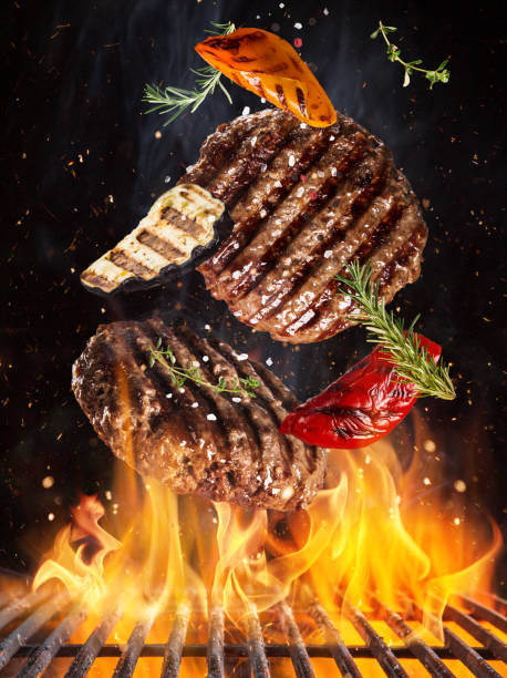 Tasty beef steaks flying above cast iron grate with fire flames. stock photo